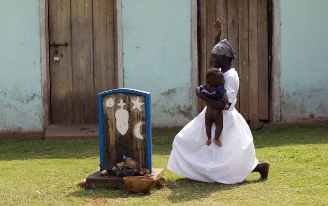 A follower of the Holy Spirit Movement church performs rituals on a child at a shrine in Gulu town, north of Uganda capital Kampala February 15, 2015. (Photo by James Akena/Reuters)