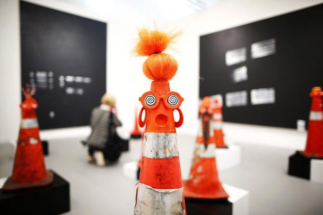 """A visitor photographs part of Robert Pruitt's """"Safety Cones"""" at the Gavin Brown's Enterprise from New York's stand at the Frieze Art Fair in central London, October 16, 2013. (Photo by Andrew Winning/Reuters)"""