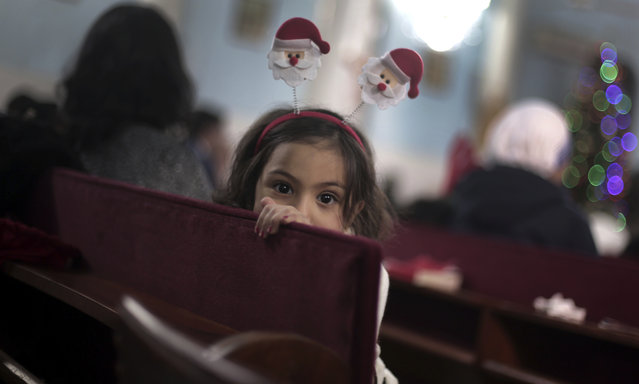 A Palestinian Christian girl attends with her family, the prayers on Christmas Eve at the Holy Family Catholic Church in Gaza City, Saturday, December 24, 2016. (Photo by Khalil Hamra/AP Photo)