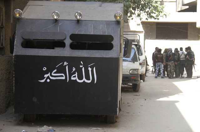 """An improvised armored vehicle is seen parked as Free Syrian Army fighters gather on a street in the refugee camp of Yarmouk near Damascus May 5, 2013. The Arabic on the vehicle reads: """"God is great"""". (Photo by Ward Al-Keswani/Reuters)"""