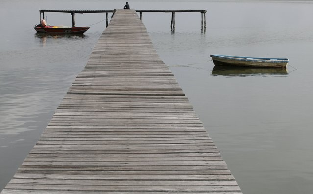 A resident sits at the end of the jetty at a water village on Malaysia's island of Labuan in this February 7, 2012 file photo. Malaysia is expected to report trade data this week. (Photo by Bazuki Muhammad/Reuters)
