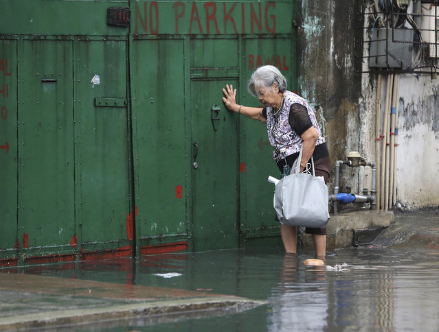 A Filipino woman crosses floodwaters caused by rains from Typhoon Nock-Ten in Quezon city, north of Manila, Philippines on Monday, December 26, 2016. (Photo by Aaron Favila/AP Photo)