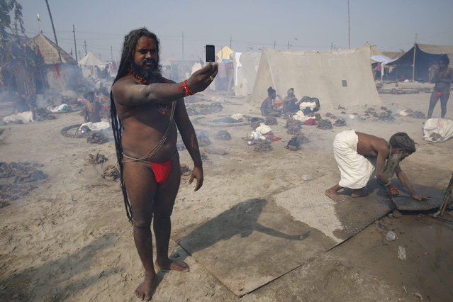 "A Hindu holy man photographs himself on a mobile phone at Sangam, the confluence of rivers the Ganges and Yamuna at the annual traditional fair ""Magh Mela"" in Allahabad, India, Tuesday, February 4, 2014. (Photo by Rajesh Kumar Singh/AP Photo)"