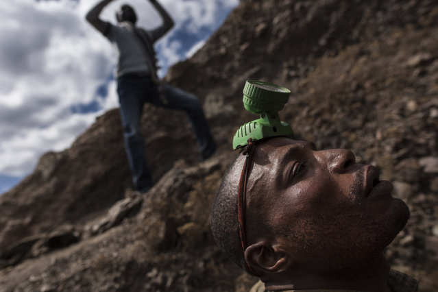 "A ""creuseur"", or digger, a plastic lantern on his head, readies to enter a copper and cobalt mine in Kawama, Democratic Republic of Congo on June 8, 2016. Cobalt is used in the batteries for electric cars and mobile phones. Working conditions are dangerous, often with no safety equipment or structural support for the tunnels. The diggers say they are paid on average US$2-3/day. (Photo by Michael Robinson Chavez/The Washington Post)"
