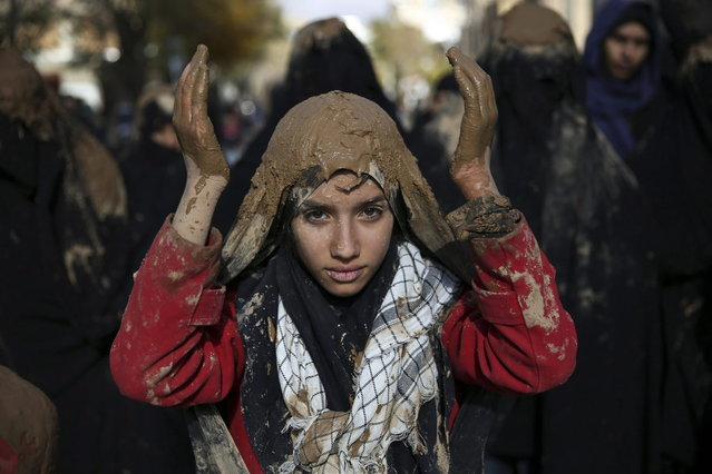 An Iranian Shiite covers her head with mud during Ashoura rituals, marking the death anniversary of Imam Hussein, the grandson of Islam's Prophet Muhammad, at the city of Bijar, west of the capital Tehran, Iran, Thursday, November 14, 2013. Hussein, one of Shiite Islam's most beloved saints, was killed in a 7th century battle at Karbala, Iraq. (Photo by Ebrahim Noroozi/AP Photo)