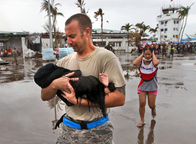Air Force TSgt. Jody Dessicino of Egg Harbor, New Jersey, helps a mother carry her baby to board an evacuation flight at the airport in Tacloban, Philippines, Friday, November 22, 2013. Hundreds of thousands of people were displaced by Typhoon Haiyan, which tore across several islands in the eastern Philippines on November 8. (Photo by Dita Alangkara/AP Photo)