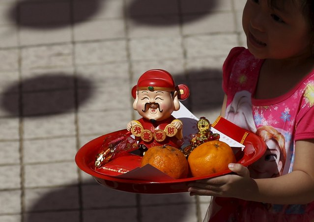 A child holds an offering at a temple during Chinese New Year celebrations in Kuala Lumpur, Malaysia, February 8, 2016. (Photo by Olivia Harris/Reuters)