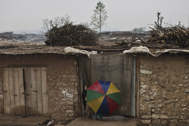 An Afghan refugee girl holds an umbrella while she and two other children stand in the doorway of a mud home during rainfall on the outskirts of Islamabad, Pakistan, Friday, February 20, 2015. (Photo by Muhammed Muheisen/AP Photo)