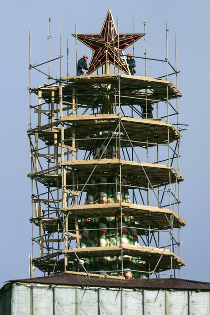 Workers stand on scaffolding around the top of the Kremlin's Spasskaya Tower to renovate it, in Moscow, Russia, Tuesday, April 7, 2015. The Spasskaya Tower has been hidden from view for repairs since December 2014. (Photo by Pavel Golovkin/AP Photo)