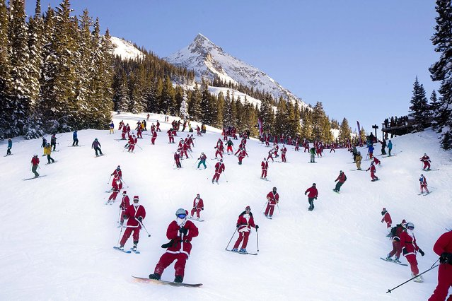 "Participants dressed as Santas ski from Uley's Ice Bar on Crested Butte Mountain, Crested Butte, Colo., for the first ""Santa Ski Crawl"" on December 14. There were over 425 in participants in this event. (Photo by Nathan Bilow/Crested Butte Mountain Resort)"