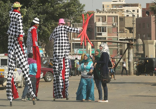 Girls talk to men on stilts before they perform in a street as Egyptians celebrate the spring holiday of Sham el Nessim in Cairo, April 13, 2015. (Photo by Asmaa Waguih/Reuters)