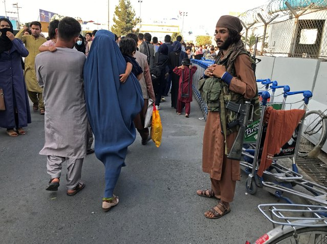 A member of Taliban stands guard as people walk at the entrance gate of Hamid Karzai International Airport in Kabul, Afghanistan, August 16, 2021. (Photo by Reuters/Stringer)