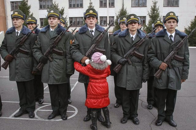 A girl hugs her brother, a recruit from the presidential regiment, as he takes the oath at a military base in Kiev November 16, 2013. (Photo by Gleb Garanich/Reuters)