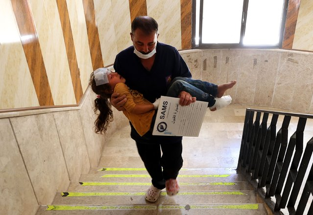 A man carries a girl that was injured during aerial bombardment at a make-shift camp for displaced Syrians, along a stairway in a hospital in the atby town of Maaret Misrin in the north of Syria's rebel-held Idlib province on September 7, 2021. (Photo by Omar Haj Kadour/AFP Photo)