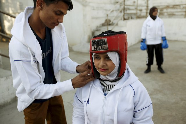 Assistant boxing coach Nadir helps Urooj, 15, put on her headgear before the start of her bout during the Sindh Junior Sports Association Boxing Tournament in Karachi, Pakistan February 21, 2016. (Photo by Akhtar Soomro/Reuters)
