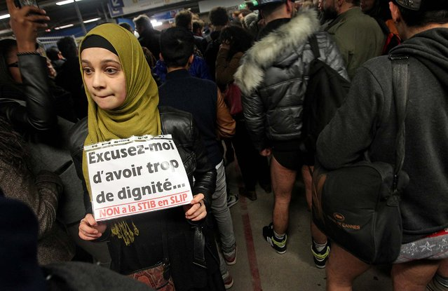 """A woman holds a sign that reads: """"Excuse me to have too much dignity, no to the public Brussels transport in underwear"""", as participants around her take part in the No Pants Metro Ride in Brussels. (Photo by Yves Logghe/Associated Press)"""