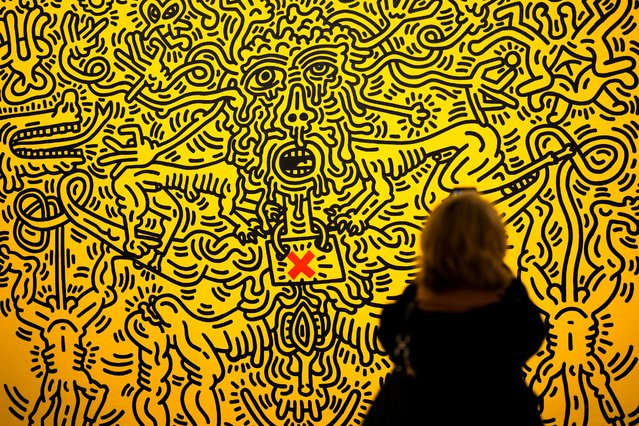 """A woman takes a picture of the painting """"Aids"""" by Keith Haring, displayed at the exhibition The Cool and the Could – Paintings from the United States and the Soviet Union 1960-1990 from the Ludwig Collection at the Martin-Gropius-Bau Museum in Berlin, Germany, Thursday, September 23, 2021. (Photo by Markus Schreiber/AP Photo)"""