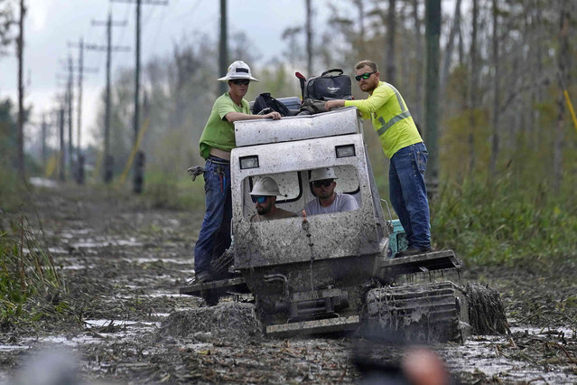 Electrical workers ride through marsh in a marsh buggy to restore power lines in the aftermath of Hurricane Ida in Houma, La., Friday, September 17, 2021. The Louisiana terrain presents special challenges like just getting out to some of the areas where power poles and lines need to be fixed. In some areas lines thread through thick swamps that can only be accessed by air boat or specialized equipment like a marsh buggy. Linemen don waders to climb into chest-high muddy waters also home to alligators and water moccasins. (Photo by Gerald Herbert/AP Photo)
