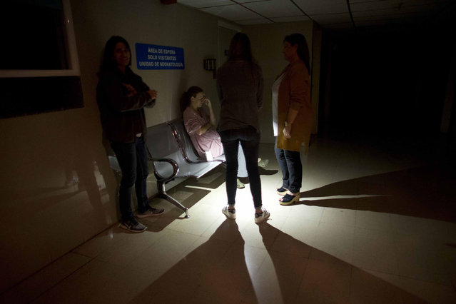 Mothers and relatives wait outside of an intense care room for babies at a clinic, during a power outage in Caracas, Venezuela, Thursday, March 7, 2019. A power outage left much of Venezuela in the dark early Thursday evening in what appeared to be one of the largest blackouts yet in a country where power failures have become increasingly common. (Photo by Ariana Cubillos/AP Photo)
