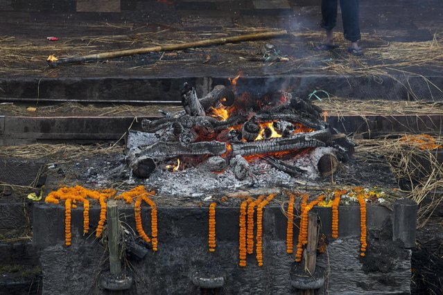 The last flames rise from a cremation pyre of a victim of Saturday's earthquake at the Pashupatinath temple on the banks of the Bagmati River in Kathmandu, Nepal, Tuesday, April 28, 2015. (Photo by Bernat Armangue/AP Photo)