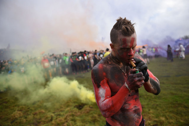 """A man with a painted torso lights a cigar before the start of the """"Tough Guy"""" adventure race near Wolverhampton, West Midlands, on January 29, 2017. The Tough Guy event, which is being held for the final time in its 30th year, challenges thousands of competitors to run a gruelling course whilst negotiating over 200 obstacles including: water, fire, and tunnels. (Photo by Oli Scarff/AFP Photo)"""