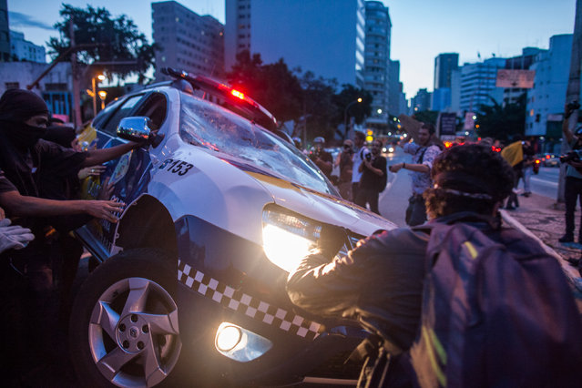 Protesters destroy a police vehicle during demonstrations against the staging of the upcoming 2014 World Cup on January 25, 2014 in Sao Paulo, Brazil. More than 100 protesters attended the demonstration. Demonstrations were planned for today in 36 Brazilian cities against the billions in spending for the games which begin June 12.(Photo by Victor Moriyama/Getty Images)
