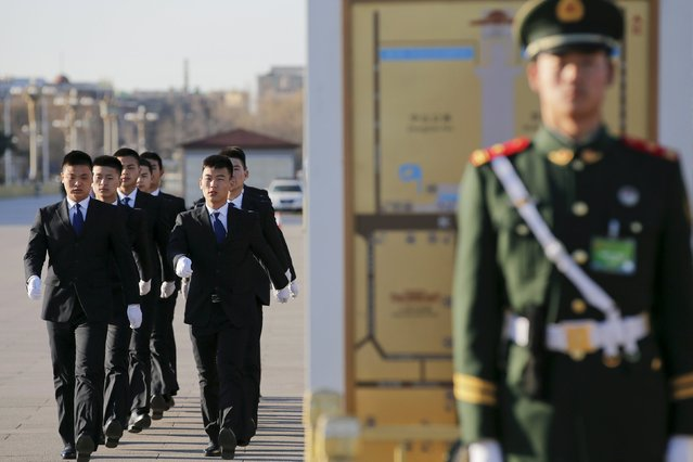 Security officers walk outside the Great Hall of the People ahead of the third plenary session of the National People's Congress (NPC), in Beijing, China, March 13, 2016. (Photo by Damir Sagolj/Reuters)