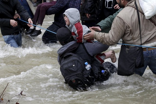 A migrant tries to stop a child from falling in the water as migrants wade across a river near the Greek-Macedonian border, west of the the village of Idomeni, Greece, March 14, 2016. (Photo by Alexandros Avramidis/Reuters)