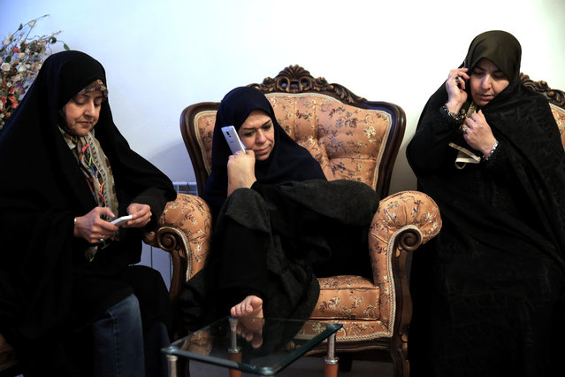In this picture taken on Saturday, January 31, 2015, Zohreh Etezadossaltaneh, center, talks on her mobile phone, held with her foot, during a meeting at her friend's home in Tehran, Iran. Now 52 years old, the retired Iranian teacher who was born without arms has dedicated herself to helping others with similar disabilities live full and satisfying lives. (Photo by Ebrahim Noroozi/AP Photo)