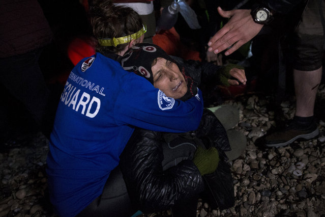 A volunteer hugs a woman who cries for her unconscious husband after an overcrowded boat was carrying dozens of migrants and refugees from nearby Turkey arrived at the shore of the northeastern Greek island of Lesbos, on Sunday, March 20, 2016. Two migrants have been found dead on that boat that on the first day of the implementation of an agreement between the EU and Turkey on handling the new arrivals. (Photo by Petros Giannakouris/AP Photo)