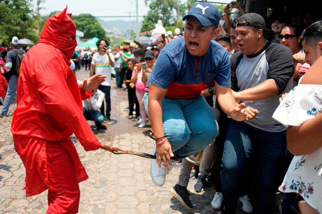 "A Catholic faithful fancy dressed as a ""talciguin"" -character of the local folklore- takes part in the celebration of an ancient local tradition that marks the start of Holy Week, in Texistepeque, some 80 km west of San Salvador, on April 15, 2019. Talciguines are devils who ""lash"" Catholic faithfuls to cleanse their sins. (Photo by Marvin Recinos/AFP Photo)"