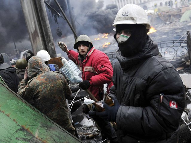 Protesters hold petrol bombs during clashes with police in Kiev , on February 20, 2014. (Photo by Louisa Gouliamaki/AFP Photo)
