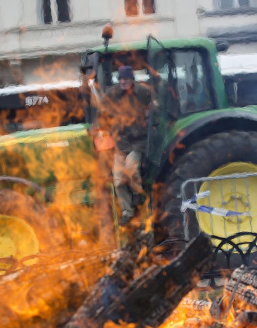 Dairy farmers stand by their tractors in front of a bonfire during a demonstration against the lifting of milk quotas in front of the European Parliament in Brussels on Tuesday, March 31, 2015. Dairy farmers hit the streets of Brussels to protest against the lifting European Union milk quotas amid concern the move will flood the market with surplus milk. (Photo by Virginia Mayo/AP Photo)