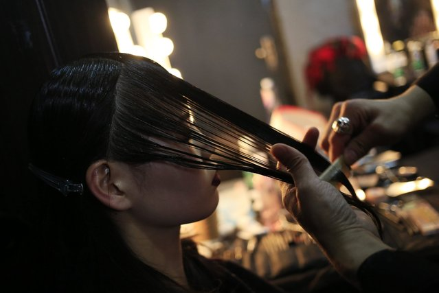 A model has her hair done backstage before a fashion show by Greek designer Mary Katrantzou during the Mercedes-Benz China Fashion Week in Beijing, China, 27 March 2016. The fashion week runs until 31 March. (Photo by How Hwee Young/EPA)