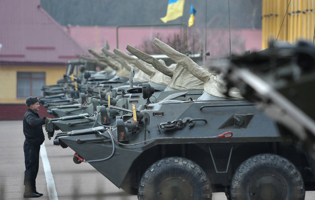 An Ukrainian soldier inspects armored vehicles on a military base in Lviv, Ukraine, 03 March 2014. Ukraine put its armed forces on 'full combat readiness' and called up reserves, as Russian military activity increased on both sides of the border. The Russian army reportedly occupied key sites in the autonomous region of Crimea, where a majority of the population is ethnic Russian. (Photo by Ivan Boberskyy/EPA)