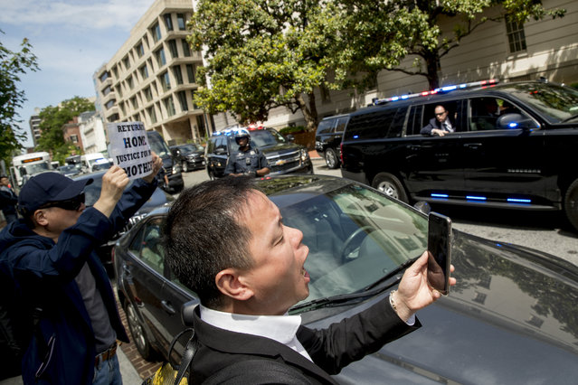 Protesters shout as the motorcade carrying Chinese Vice Premier Liu He and his delegation depart the Office of the United States Trade Representative in Washington, Friday, May 10, 2019, following trade talks between the United States and China. (Photo by Andrew Harnik/AP Photo)