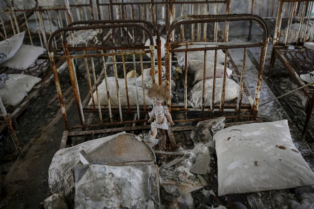 A doll is seen amongst beds at a kindergarten in the abandoned city of Pripyat near the Chernobyl nuclear power plant in Ukraine on March 28, 2016. Deadly radiation still spews from Chernobyl 30 years after the worst nuclear meltdown in history, as a newly built giant arch is pulled into place to cover the stricken reactor for the next century. (Photo by Gleb Garanich/Reuters)