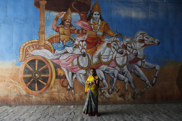 An Indian woman displays indelible mark on her finger after casting vote standing next to a mural depicting a scene from the Hindu epic Mahabharata in Prayagraj, Uttar Pradesh state, India , Sunday, May 12, 2019. Indians are voting in the next-to-last round of 6-week-long national elections, marked by a highly acrimonious campaign with Prime Minister Narendra Modi flaying the opposition Congress party rival Rahul Gandh's family for the country's ills. (Photo by Rajesh Kumar Singh/AP Photo)