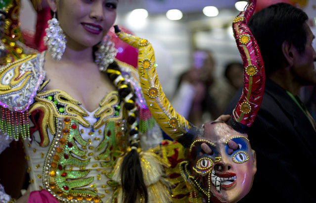 A contestant holds her mask as she waits to compete in the Queen of Great Power contest, in La Paz, Bolivia, Friday, May 24, 2019. (Photo by Juan Karita/AP Photo)