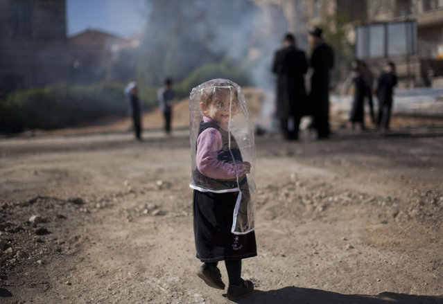 An Ultra-Orthodox Jewish girl wears a plastic cover to protect her from the smoke as others burn leavened items in a final preparation before the Passover holiday, in Jerusalem, Wednesday, April 8, 2009. (Photo by Oded Balilty/AP Photo)