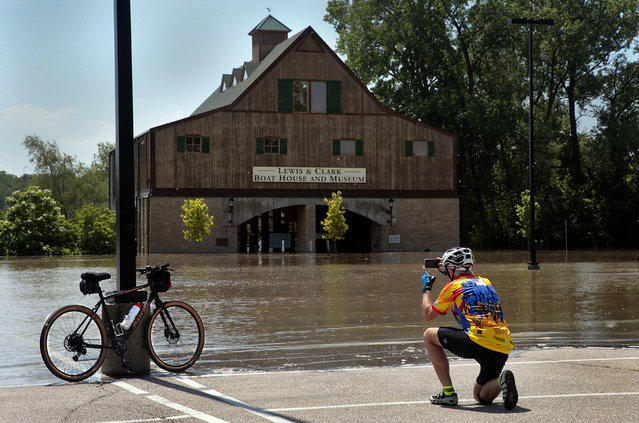 Andy Gaul of Tucson, Arizona photographs his bike in front of the flooded Lewis & Clark Boat House and Museum in Frontier Park on Friday, May 24, 2019. St. Charles officials closed the park and the Katy Trail due to Missouri River flooding, moving a weekend Irish Fest to New Town St. Charles. (Photo by Robert Cohen/St. Louis Post-Dispatch via AP Photo)