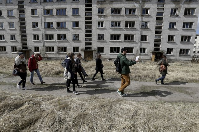 People walk past an abandoned apartment block in the ghost town of a former Soviet military radar station near Skrunda, Latvia, April 9, 2016. (Photo by Ints Kalnins/Reuters)