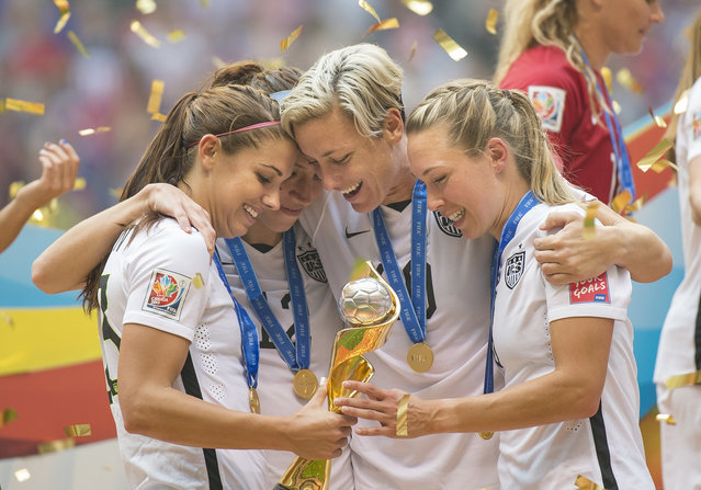 Alex Morgan (left), Lauren Holiday, Abby Wambach, and Whitney Engen of team USA celebrate with the World Cup trophy after their victory during 2015 women's World Cup Soccer in Vancouver during the final between USA and Japan. (Photo by Christopher Morris/Corbis via Getty Images)