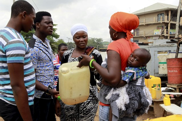 A woman with a baby on her back talks to others about her need for petrol to run her power generator, at the Area 10 shopping centre in Abuja, Nigeria May 25, 2015. (Photo by Afolabi Sotunde/Reuters)