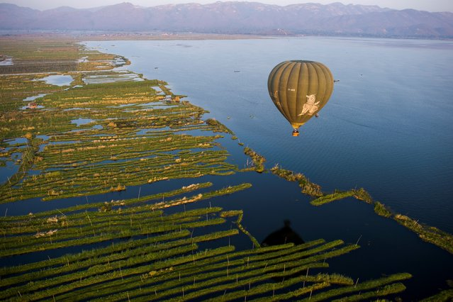 This aerial photo taken from a hot air balloon shows a hot air balloon flying over Inle lake in Shan State on February 18, 2019. (Photo by Ye Aung Thu/AFP Photo)