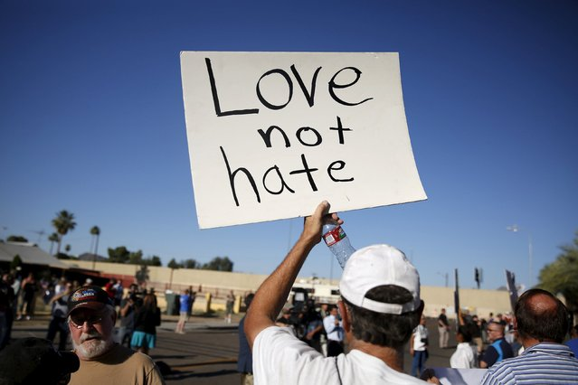 """A demonstrator holds a sign at a """"Freedom of Speech Rally Round II"""" across the street from the Islamic Community Center in Phoenix, Arizona May 29, 2015.  Arizona police stepped up security near a mosque on Friday ahead of a planned anti-Islam demonstration featuring displays of cartoons of the Prophet Mohammad, weeks after a similar contest in Texas came under attack from two gunmen.  REUTERS/Nancy Wiechec"""