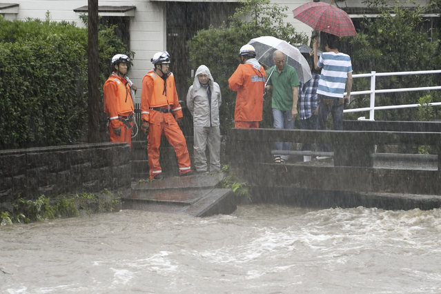 Members of the fire department monitor the water level of the Wada River in heavy rain Wednesday, July 3, 2019, in Kagoshima City, southwest Japan. Authorities have directed more than 1 million residents in parts of the southern main island of Kyushu to evacuate to designated shelters as heavy rains batter the region, prompting fears of landslides and widespread flooding. (Photo by Kyodo News via AP Photo)