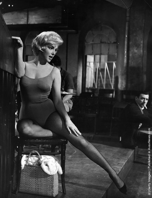 American actress Marilyn Monroe (1926  - 1962) stretches her leg under the watchful eye of Yves Montand on the set of the 20th Century Fox film Let's Make Love