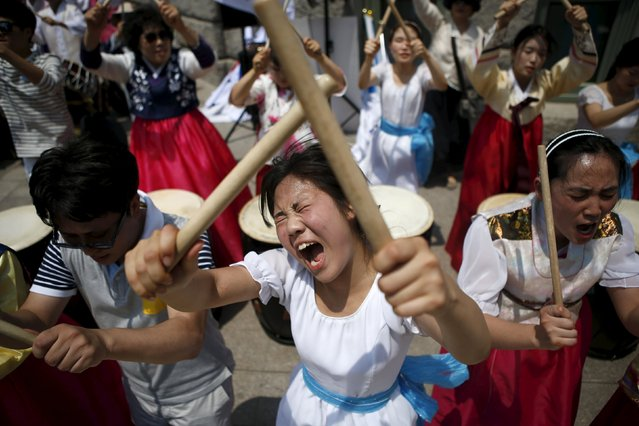 A Christian (C) yells as she and others beat traditional drums during a protest against homosexuality during Korea Queer Festival 2015 in central Seoul, South Korea, June 28, 2015. Several hundreds gays, lesbians and transgender people held the gay pride march to push for their rights. (Photo by Kim Hong-Ji/Reuters)