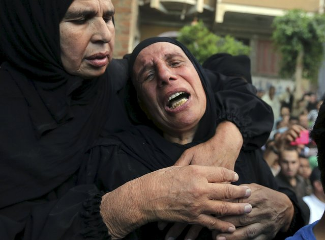 Relatives of 21-year-old Mohamed Adel, one of the army officers who died in yesterday's Sinai attacks, cry during the funeral in Al-Kaliobeya, near Cairo, Egypt, July 2, 2015. (Photo by Mohamed Abd El Ghany/Reuters)